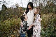 Happy siblings with mother standing at park - CAVF54794