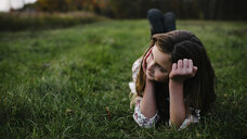Thoughtful girl lying on grassy field at park - CAVF54803