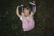 High angle view of playful girl lying on grassy field at park - CAVF54818