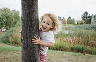 Portrait of cute happy girl standing by tree at park - CAVF54821