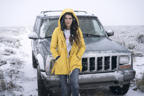 Portrait of woman standing by off-road vehicle on field during winter - CAVF54827