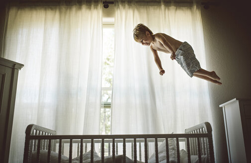 Shirtless boy levitating over crib against window at home - CAVF54830