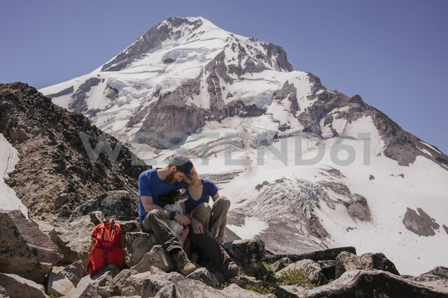 Full length of couple with dog sitting on mountain during winter - CAVF54866