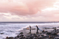Female friends carrying surfboards on shore at beach against cloudy sky - CAVF54884