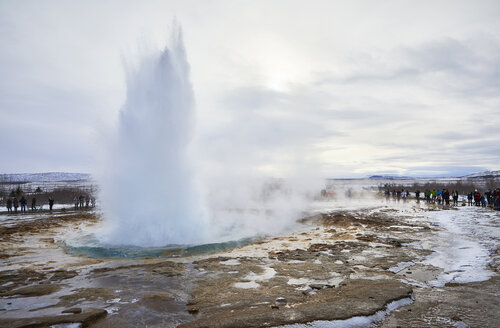 Tourists looking at water splashing from geyser against cloudy sky during winter - CAVF54914