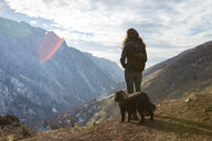 Woman with dog looking at view while standing on mountain during winter - CAVF54926