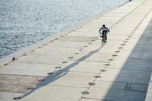 Young man riding bike on waterfront promenade at the riverside - VPIF01036