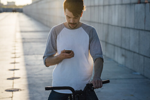 Young man with commuter fixie bike looking at cell phone - VPIF01042