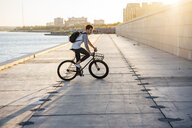 Young man with backpack riding bike on waterfront promenade at the riverside at sunset - VPIF01057