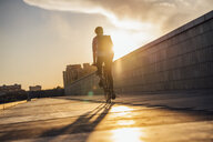 Young man with backpack riding bike on promenade at sunset - VPIF01063