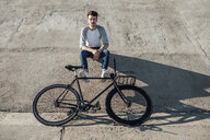 Young man with commuter fixie bike having a break sitting on concrete wall - VPIF01069