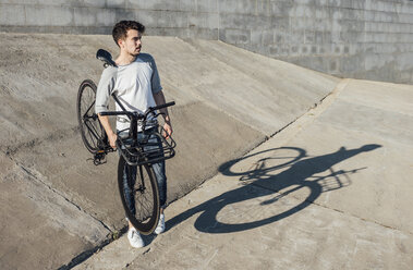 Young man carrying commuter fixie bike at concrete wall - VPIF01075