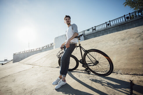 Young man with commuter fixie bike having a break at concrete wall - VPIF01078