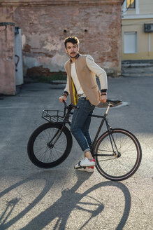 Young man with commuter fixie bike on a backyard in the city - VPIF01093