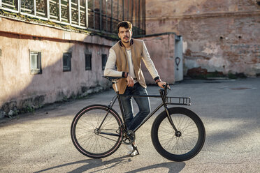 Young man with commuter fixie bike on a backyard in the city - VPIF01096