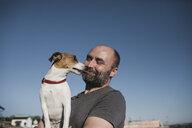 Jack Russel Terrier licking face of  smiling owner - KMKF00638