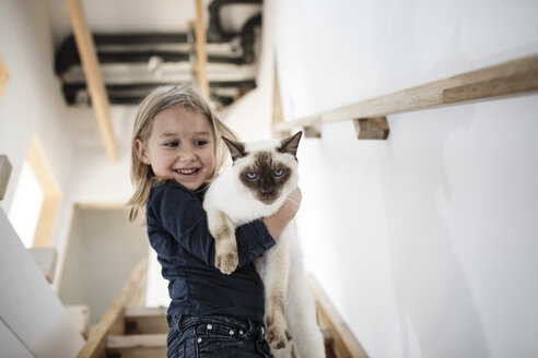 Portrait of little girl with her Siamese cat at home - KMKF00641