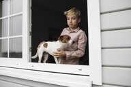 Portrait of boy with Jack Russel Terrier looking out of open window - KMKF00644