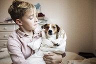 Boy with Jack Russel Terrier wrapped in blanket - KMKF00647