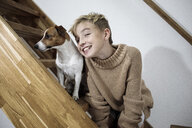 Portrait of grinning boy and his Jack Russel Terrier on stairs at home - KMKF00650