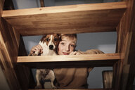 Portrait of boy with Jack Russel Terrier on stairs at home - KMKF00653
