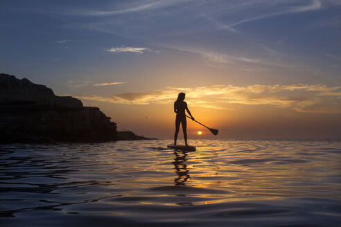 Woman paddle boarding on Pacific Ocean at sunset, San Diego, California, USA - AURF07711