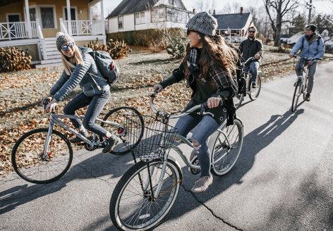 Group of friends biking through village in autumn, Portland, Maine, USA - AURF07795