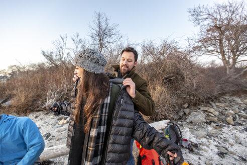 Man helping female friend put on jacket, Portland, Maine, USA - AURF07801