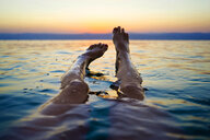 Feet of woman floating in Dead Sea at sunset, Madaba Governorate, Jordan - AURF07876