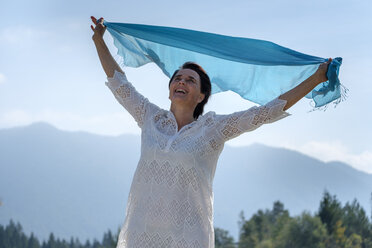 Happy woman holding swaying blue scarf at the riverside, Upper Bavaria, Germany - LBF02215