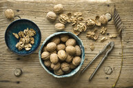 Whole and cracked walnuts in bowls on wood - ASF06255