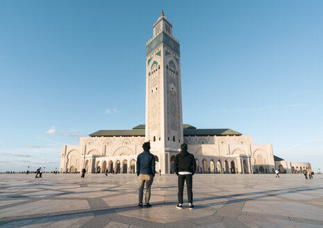 Rear view of friends standing against Mosque Hassan II - CAVF54972