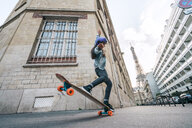 Low angle view of woman skateboarding against Eiffel Tower - CAVF54975