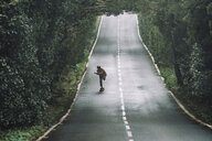 Man skateboarding on road amidst forest at Garajonay National Park - CAVF54987
