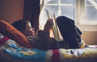 Boy with stuffed toy reading book while lying on bed at home - CAVF54990