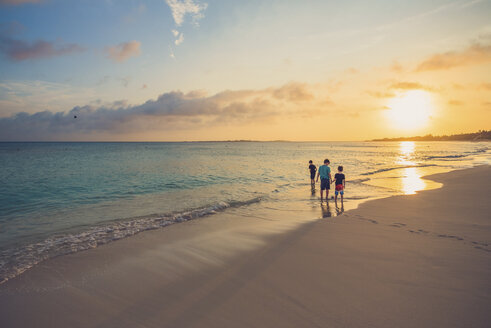 Siblings standing on shore at beach against sky during sunset - CAVF54993