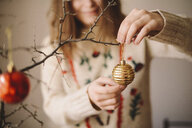 Midsection of woman hanging bauble on twig during Christmas at home - CAVF55002
