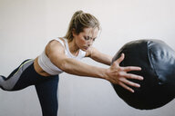 Woman carrying fitness ball while standing by wall in gym - CAVF55026