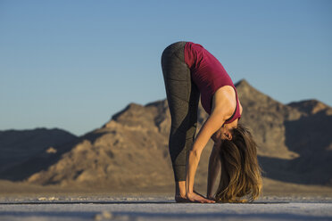 Side view of woman practicing yoga against clear blue sky during sunset - CAVF55041