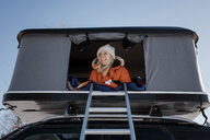 Low angle view of smiling woman sitting in roof tent on car - CAVF55056