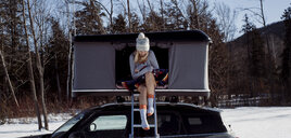 Full length of woman sitting in roof tent on car during winter - CAVF55059