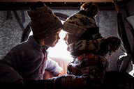 Siblings looking at each other while sitting in roof tent - CAVF55062
