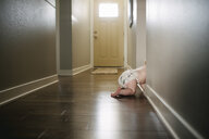 Low section of baby boy crawling on floor at home - CAVF55146