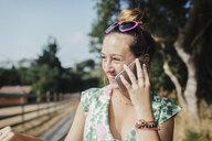 Cheerful teenage girl looking away while talking on smart phone - CAVF55149