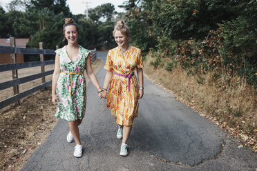 Cheerful female friends holding hands while walking on country road - CAVF55152