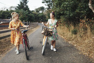 Happy friends walking with bicycles on country road - CAVF55155