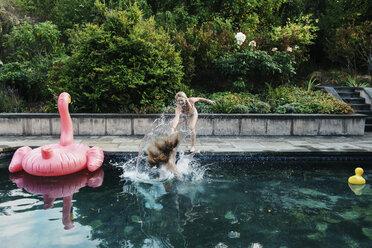 Playful teenage girl pushing friend into swimming pool - CAVF55161