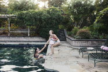 Playful teenage girl pulling friend into swimming pool standing at poolside - CAVF55164