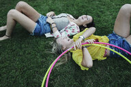 High angle view of cheerful female friends lying on grassy field with plastic hoops at park - CAVF55167