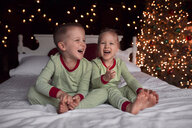 Cheerful siblings sitting on bed against illuminated Christmas Tree at home - CAVF55173